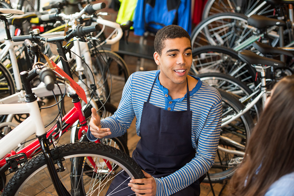 Young African-American man with a friendly smile wearing a blue and white striped shirt and black work apron, working in a bicycle shop