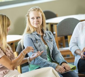Mom and teen daughter meeting with school counselor