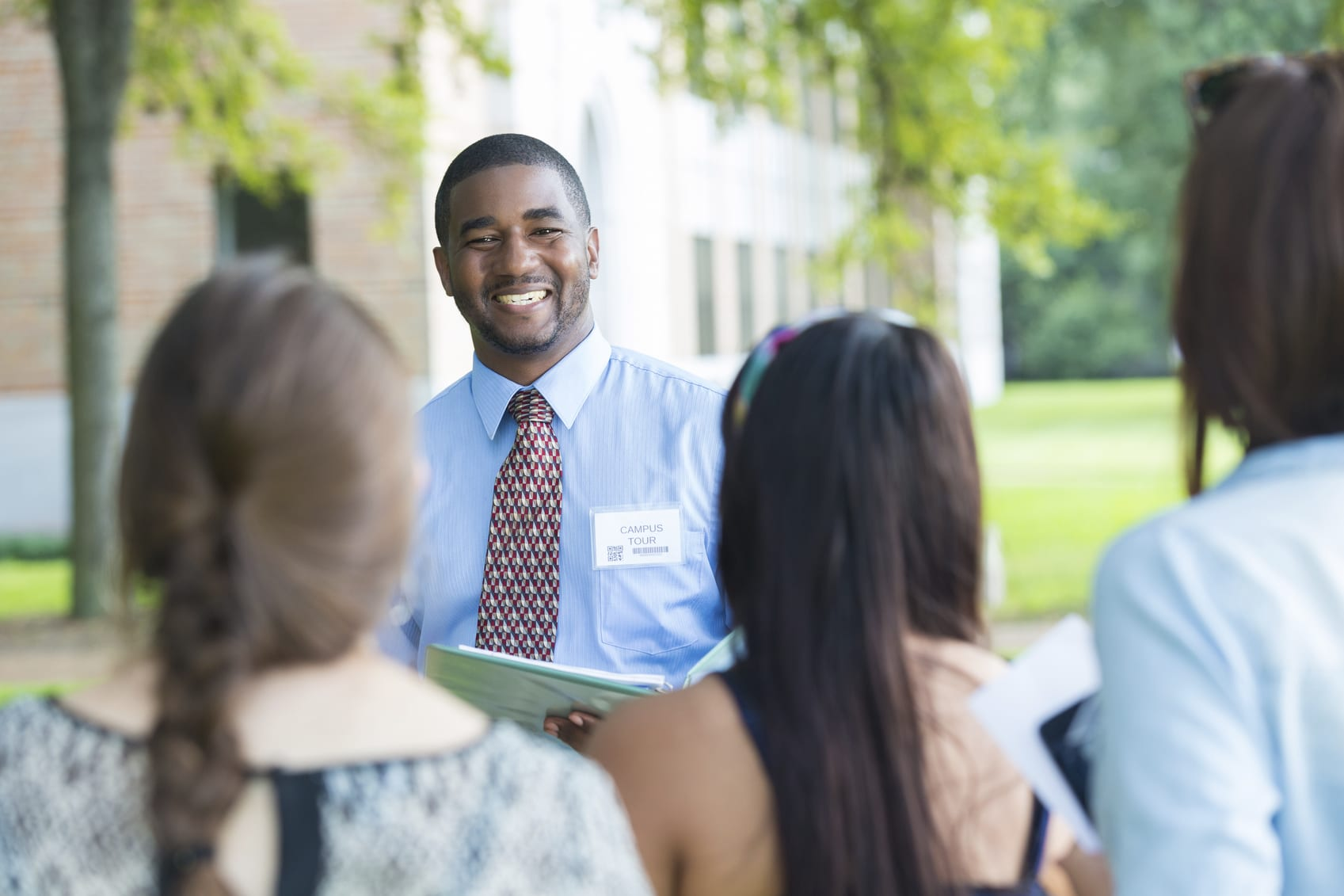College campus tour guide talking with prospective students outdoors