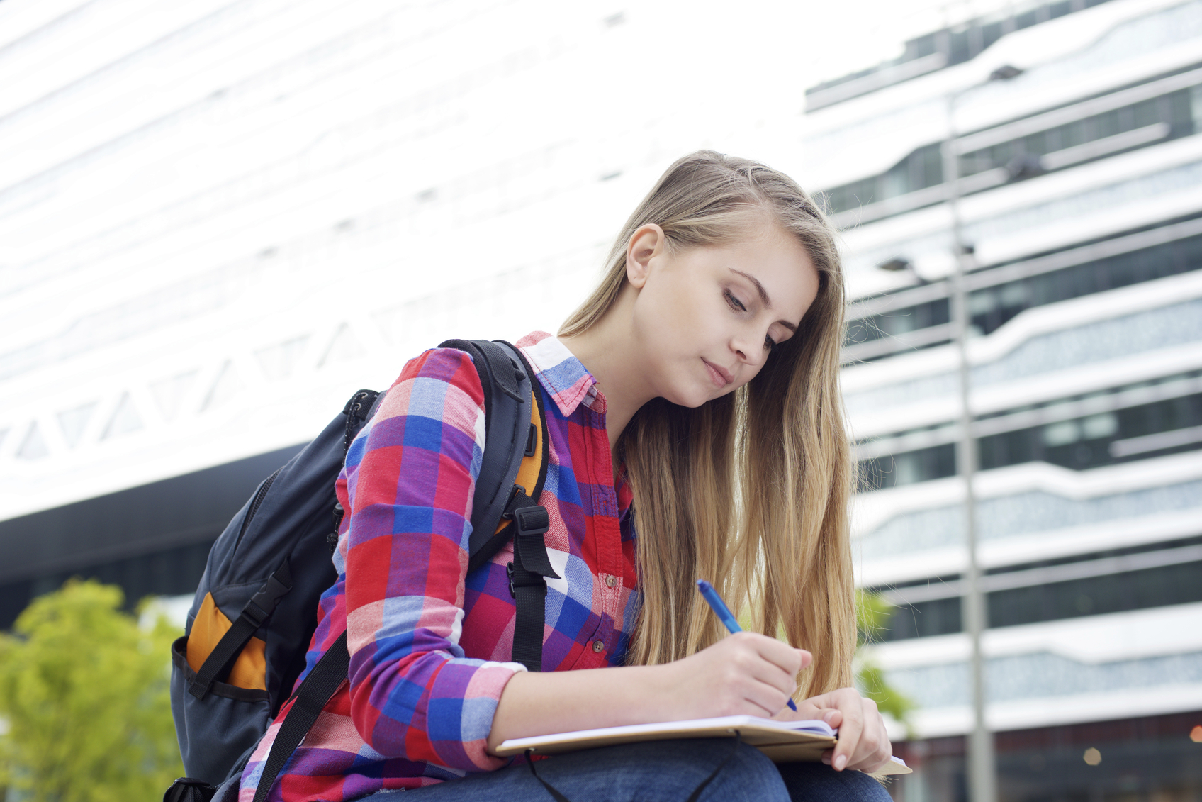Portrait of a female student sitting outside with bag and writing in book