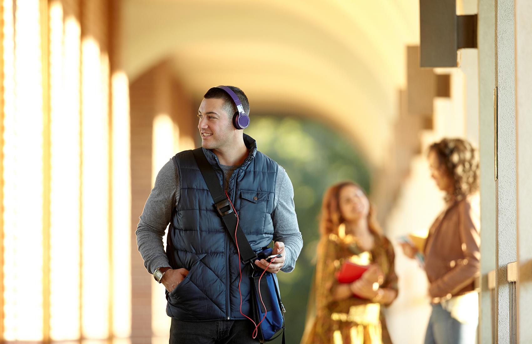 Male student walking down a campus breezeway