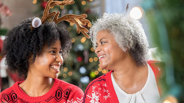 A teenager and her grandmother smile at each other and talk saving money around the holidays.