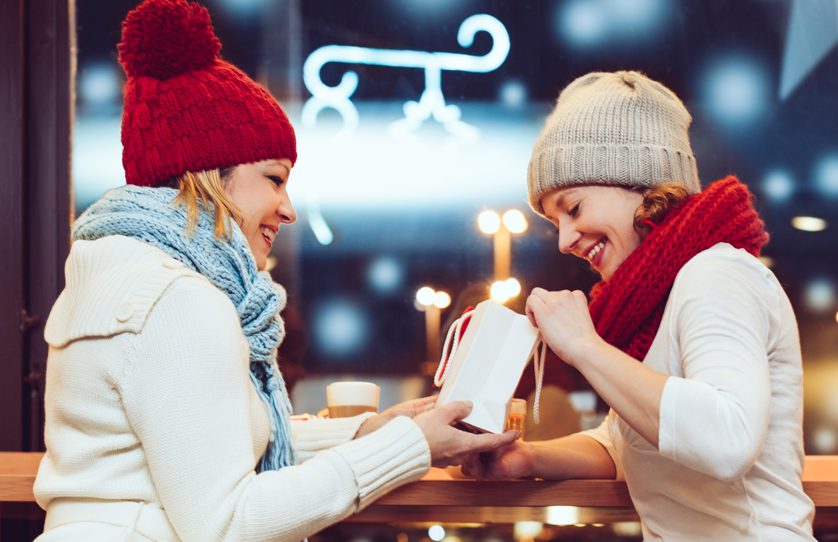 Two women in scarves and knit hats exchanging gifts