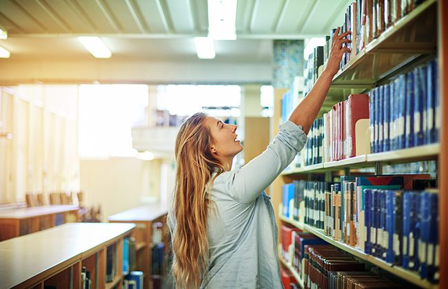 College student in library thinking about grad school