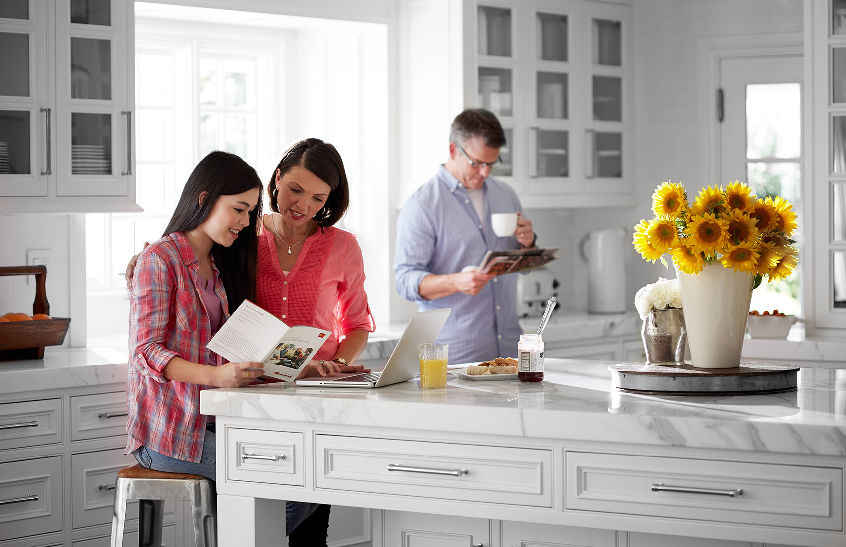 Mother and teen daughter looking at a Wells Fargo brochure in their kitchen; dad in background