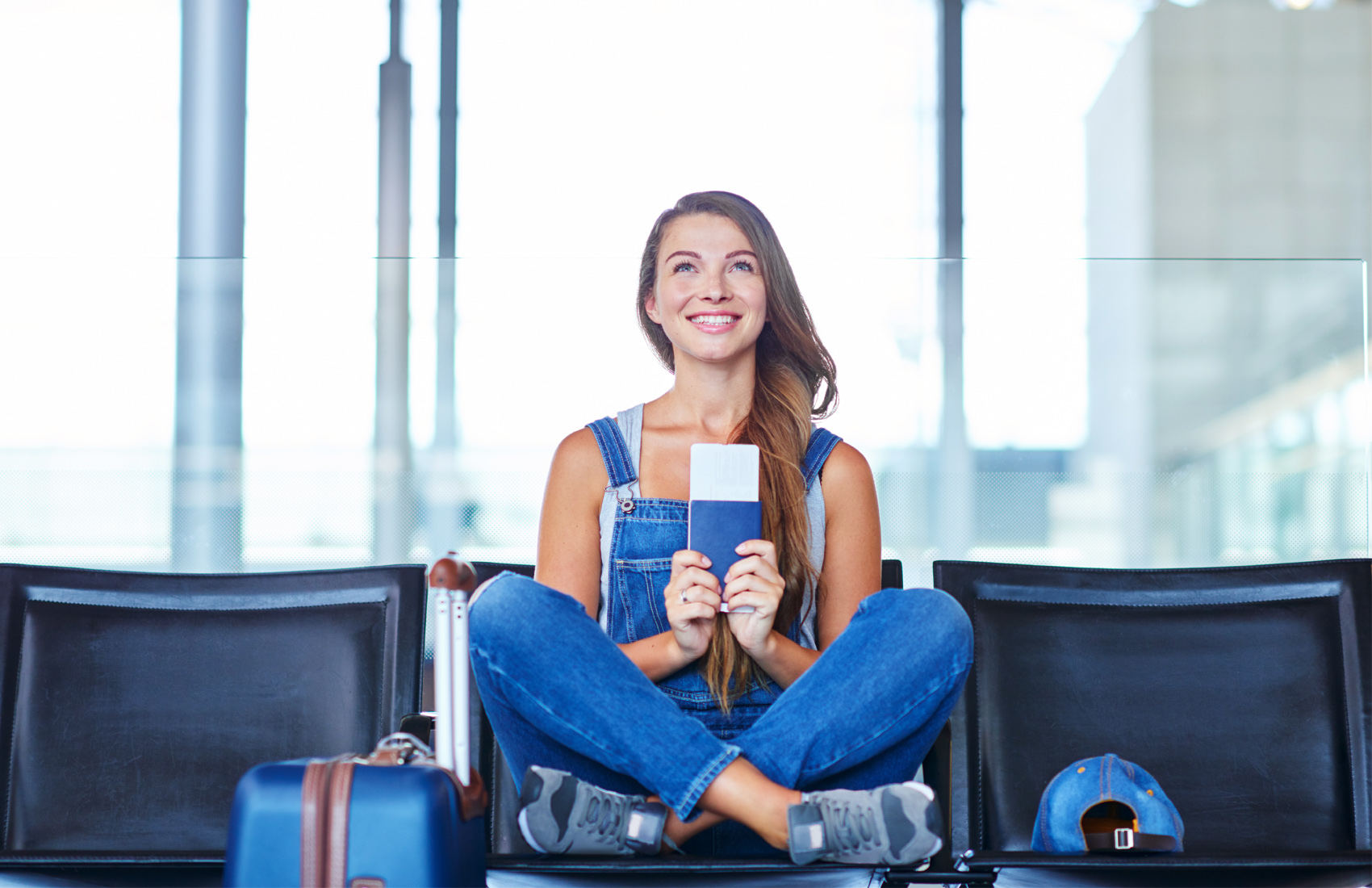 Teen girl grinning while holding ticket at airport