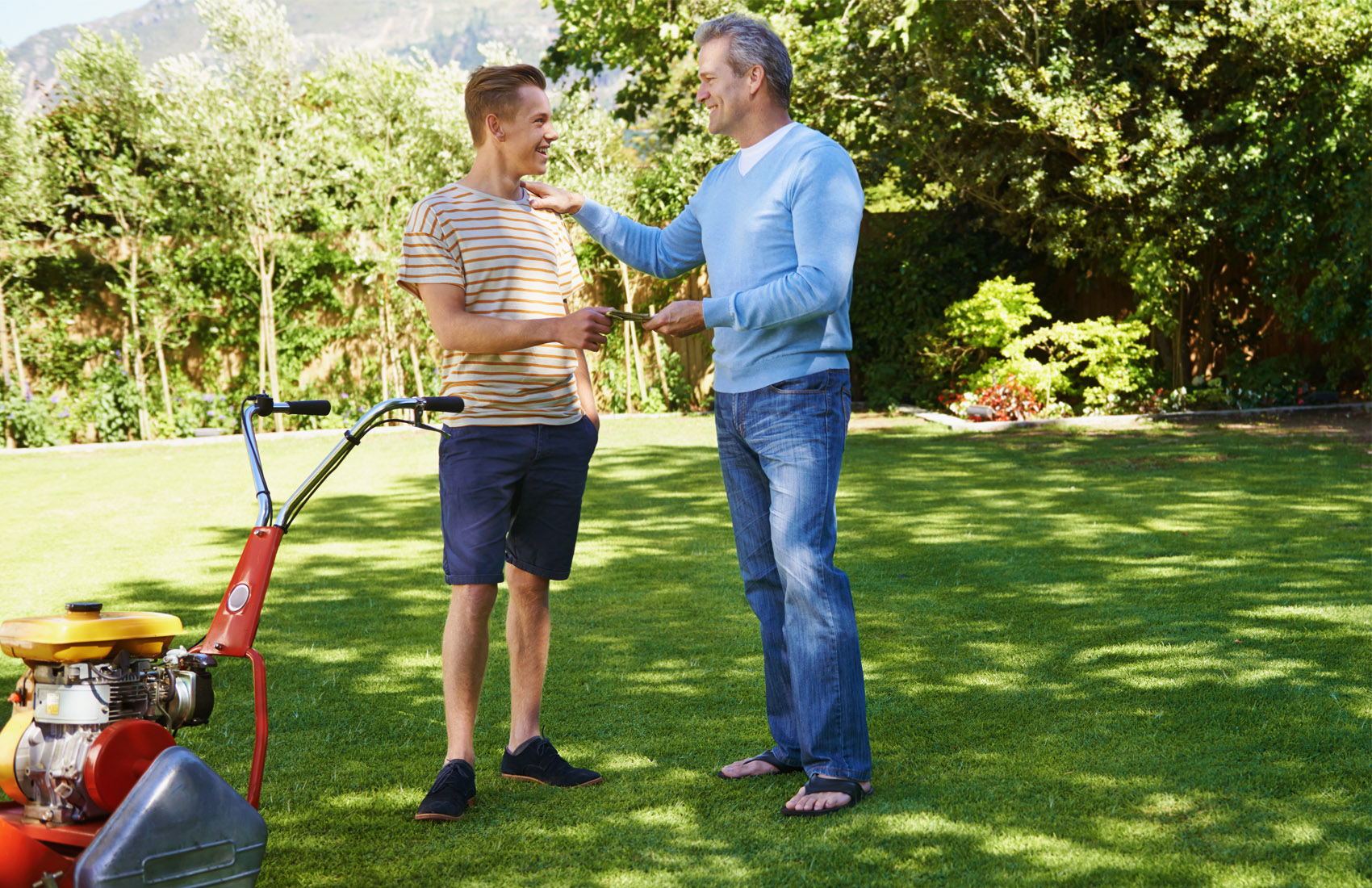 Father paying teenage son an allowance standing outside, next to a lawnmower
