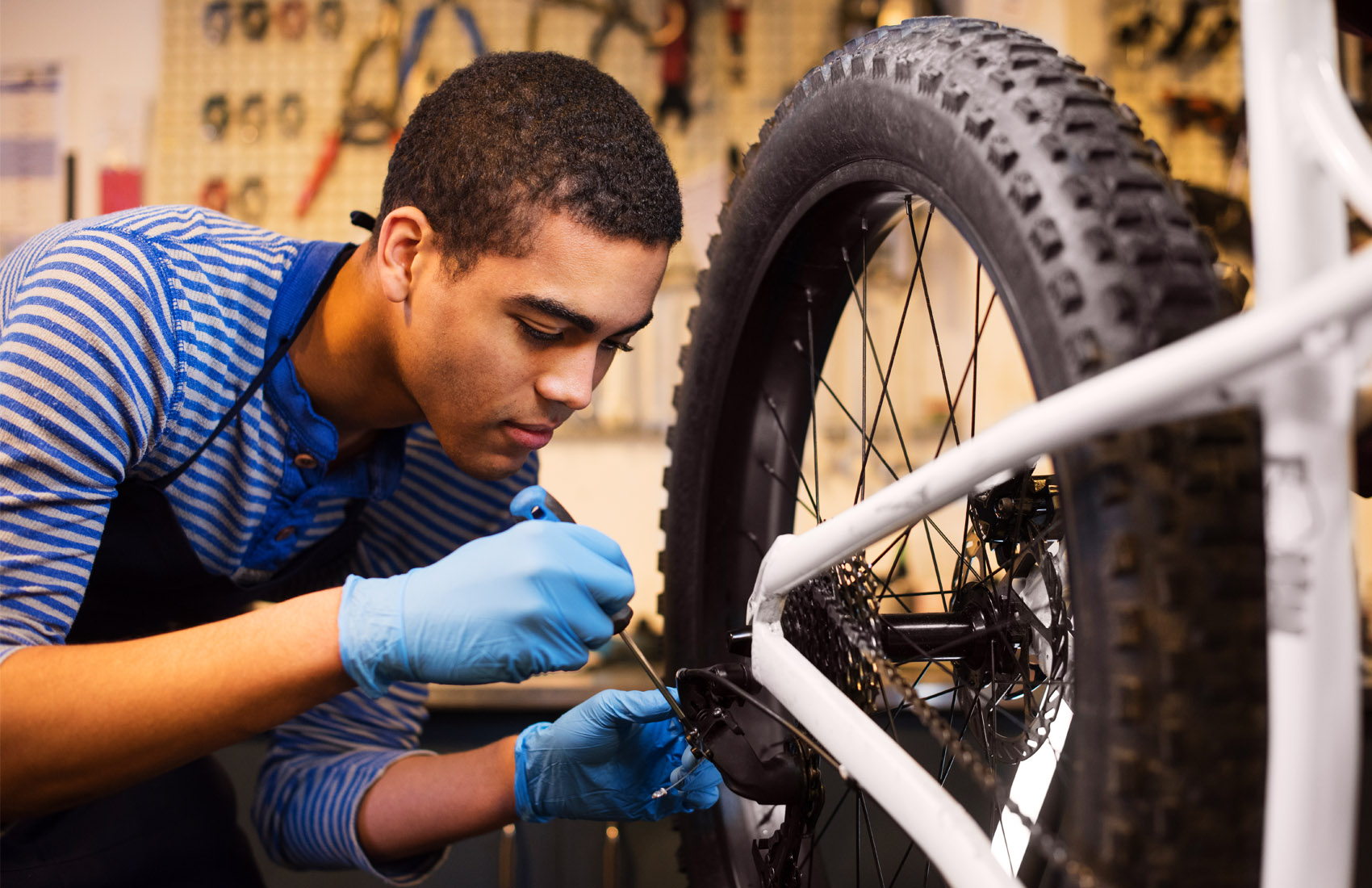 Young African American man fixing a bicycle at a repair shop