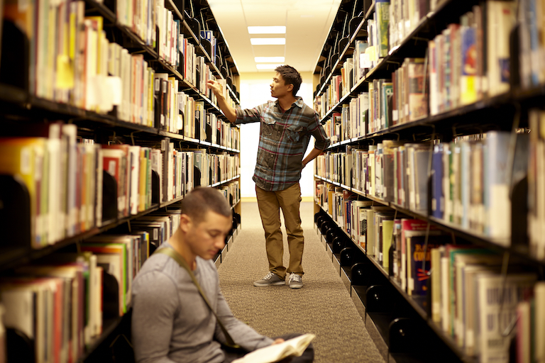 A young male student looks through book stacks.