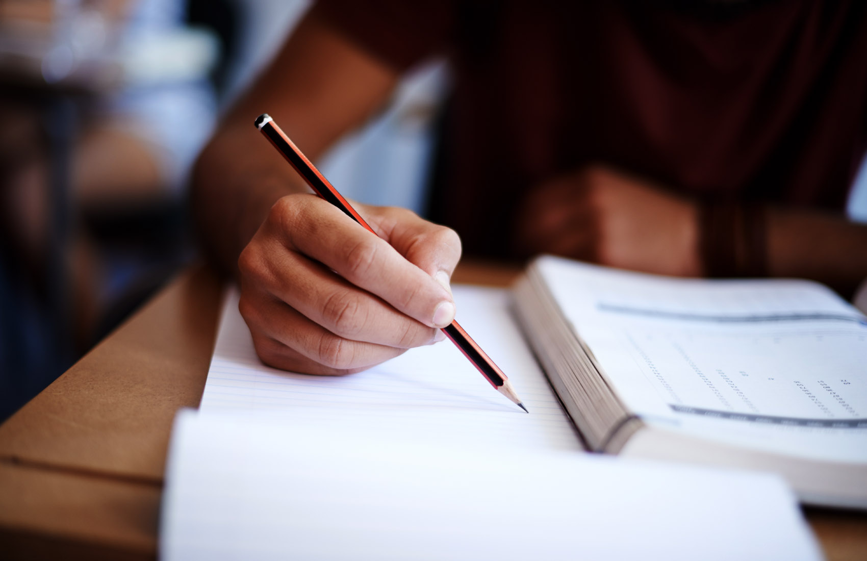 Image of student's hand holding a pencil and marking a test paper