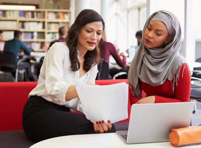 Woman and teen girl discussing paperwork in a library
