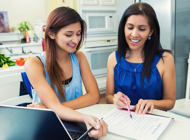 Mother and teenage daughter completing forms at a kitchen table