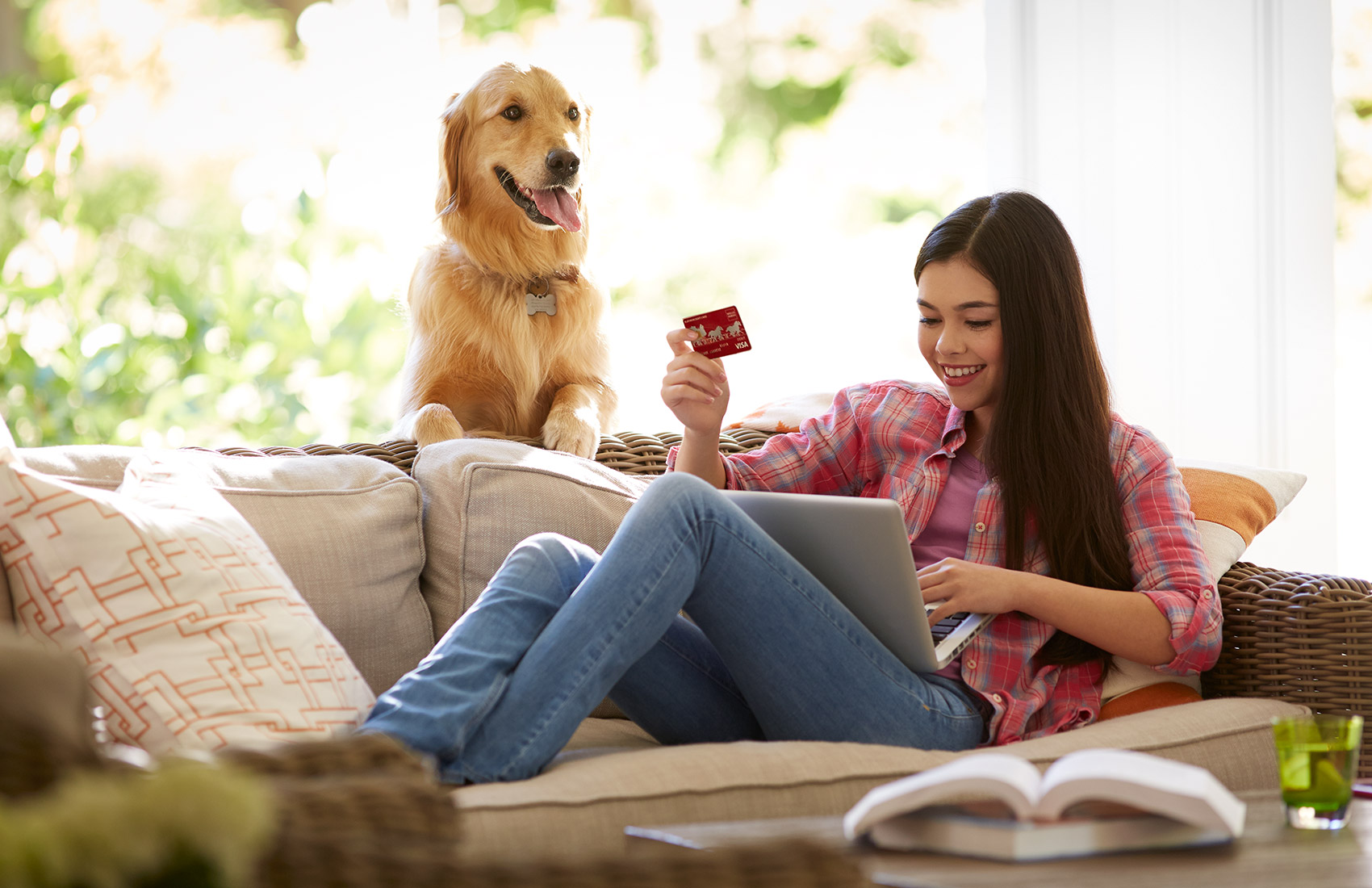 Teen girl sitting on couch and looking at laptop while holding Wells Fargo credit card