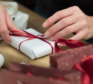 Close-up of female hands tying ribbon around present