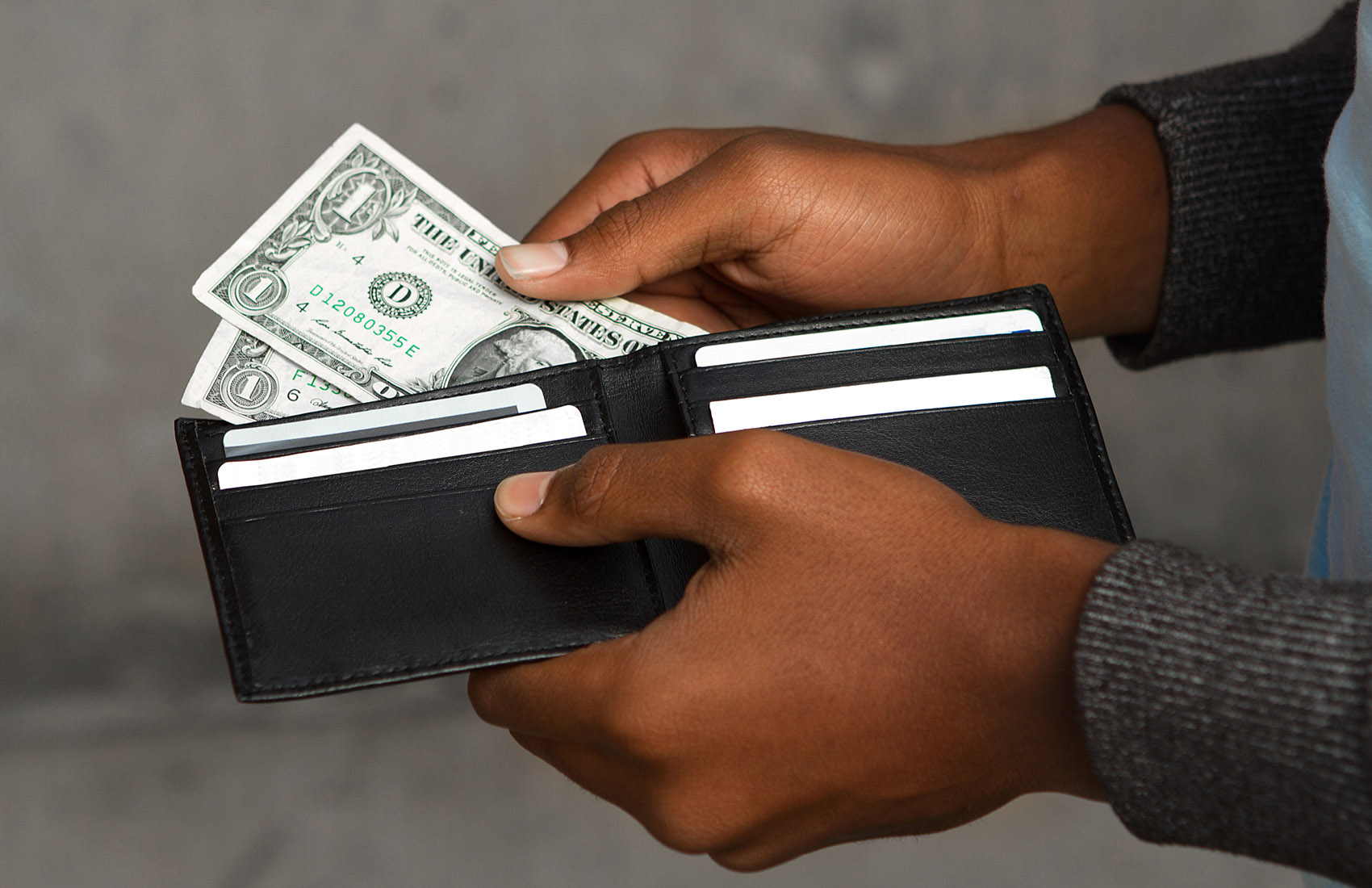 Young African American teen with very little money in his wallet.
