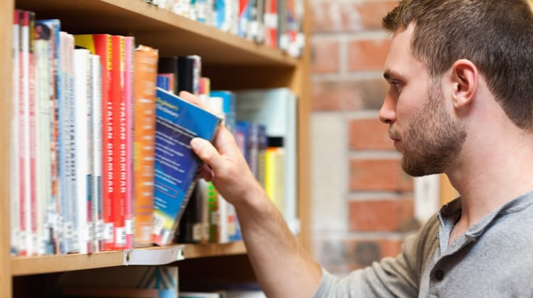 A young man grabs a book from a bookshelf.