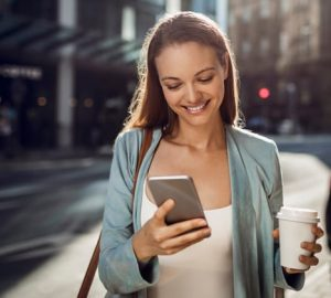 young woman holding coffee on her way to first job