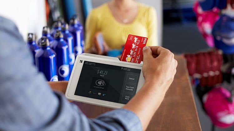 A person swipes their debit card.