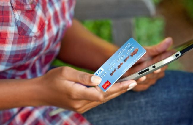 A young person holds a credit card.
