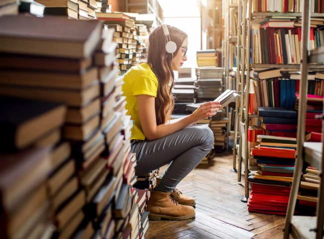 Young woman student listening to the music sitting on the heap of books