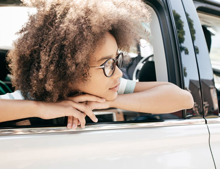 young woman looking out car window