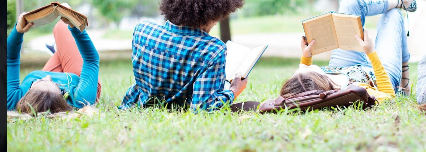 students on campus lawn reading