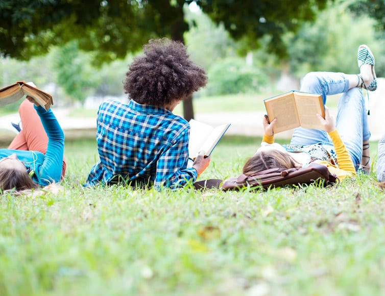 students reading on campus lawn
