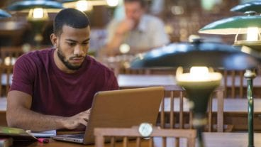 college student on laptop in library