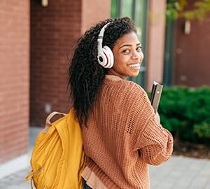 A young woman smiles back at the camera as she walks on a college campus.