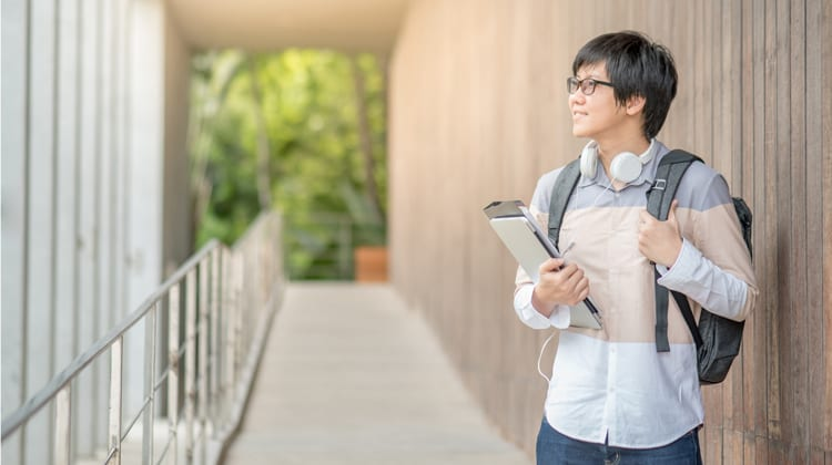 A male college student carries books and walks on campus.
