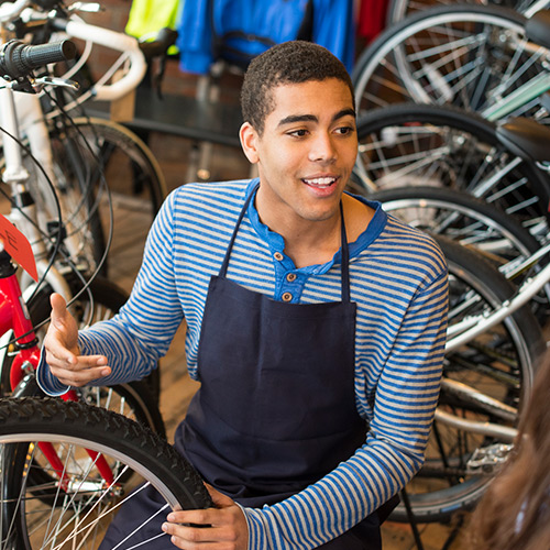 A young man works in a bike shop