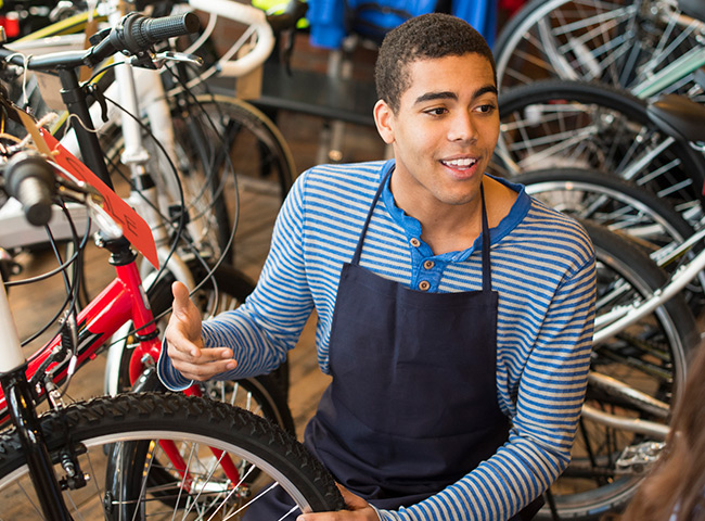 A young man works in a bike shop.