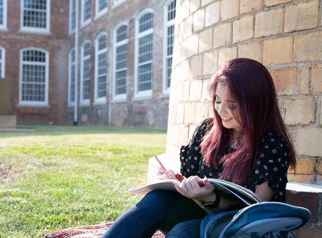 A female student studies outside.