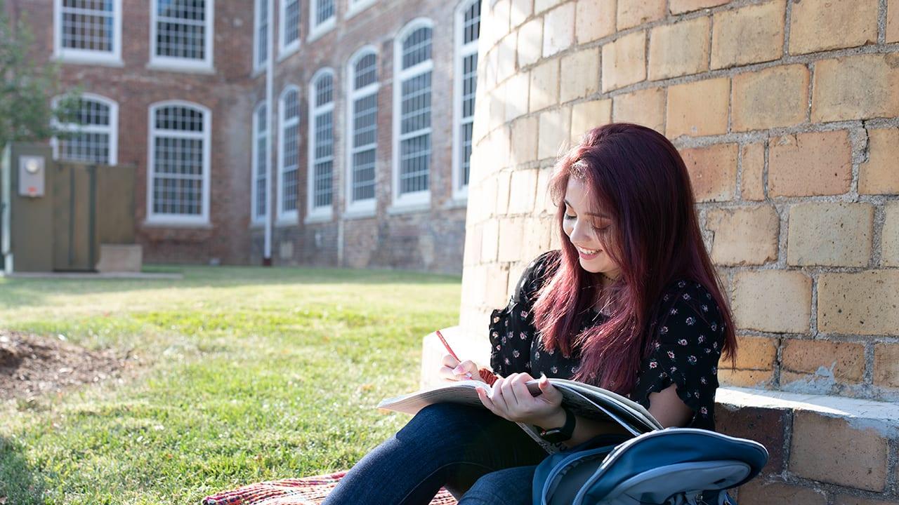 A female student studies outside.
