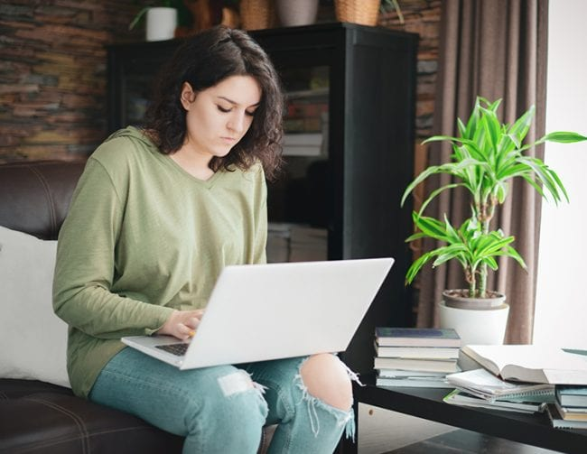 A student works at her computer while at home.