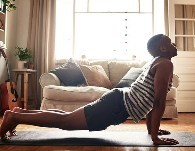A college student performs a yoga pose at home.