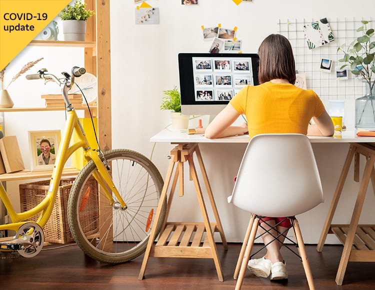 A student sits at a desk while working a summer job from home.