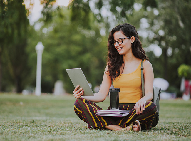Female college student reads student load information on campus