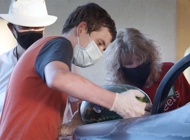 Three Wells Fargo volunteers work at a food bank.