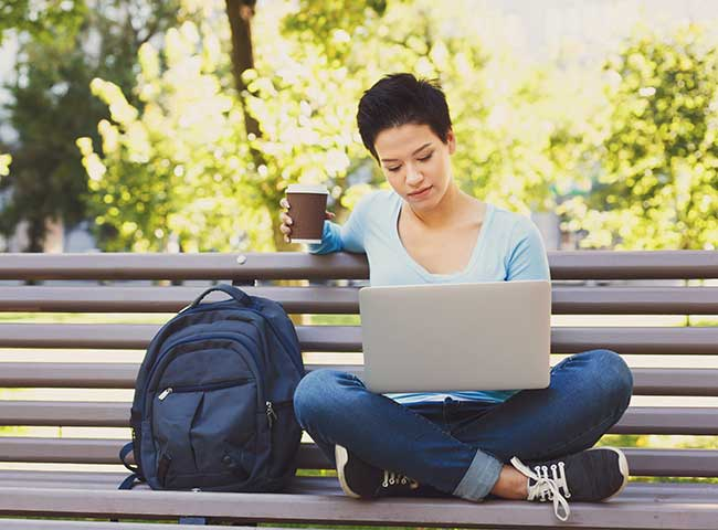A student sits on a bench with a laptop and a cup of coffee.