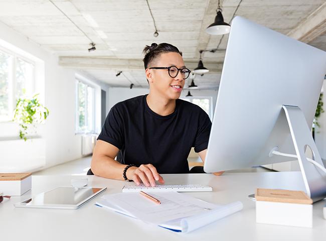 A young man watches a webinar on a desktop computer.
