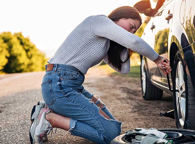 Young woman changes a car tire