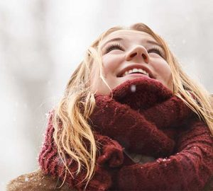 Young woman wearing a scarf looks up at snow falling.