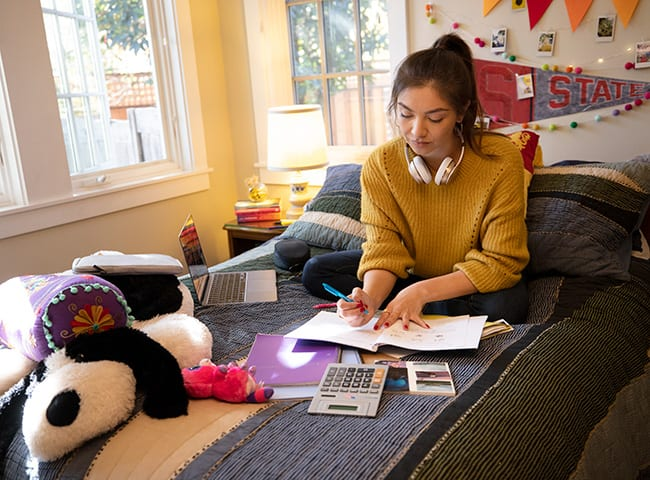 A student completes homework on her bed.