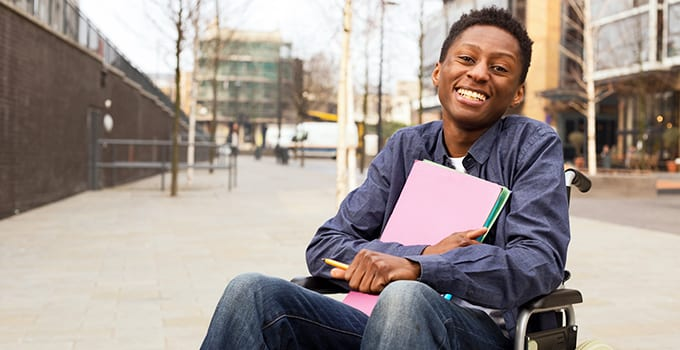 A student who uses a wheelchair holds folders in his arms and smiles.