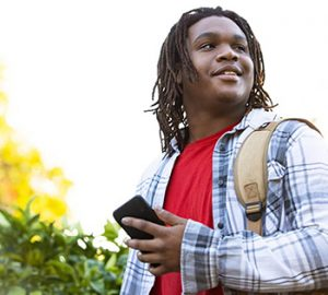 young man with backpack and cell phone outdoors