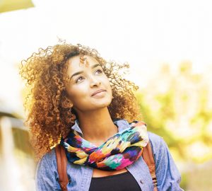 A young woman wearing a scarf stares into the distance outside