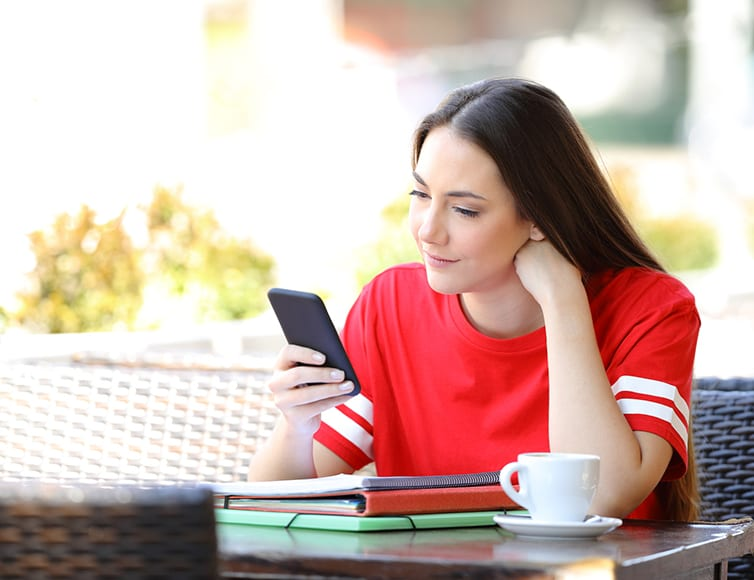 Young woman looks at her cell phone while sitting outside