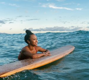 A young woman in the ocean smiles as she rests her arms on a surfboard.