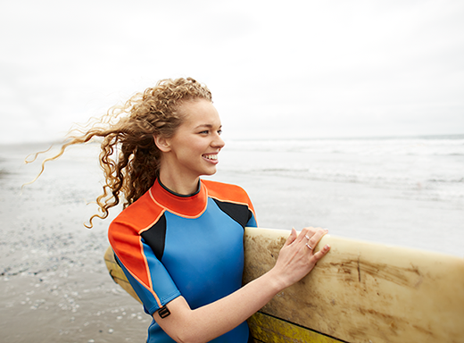 Woman holds a surfboard